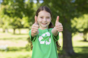 Happy little girl in green with thumbs up on a sunny day