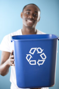 An African American young adult man holds out a recycling bin. Selective focus is on the recycling bin.
