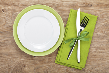 Fork with knife, blank plates and napkin. On wooden table background